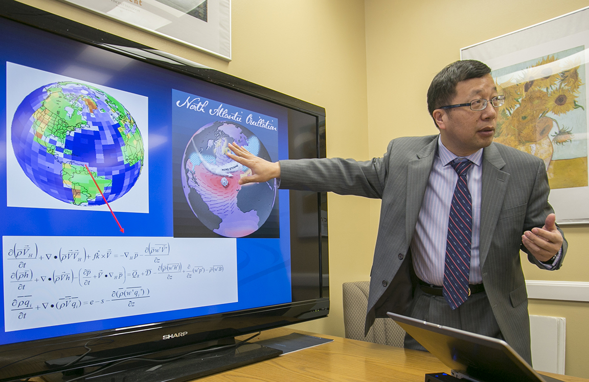 Stony Brook, NY; Stony Brook University: SoMAS Dean and Director of the MSRC Minghua Zhang discusses a slide representing reconstructed rainfall patterns that show decreasing precipitation in the northern tropics over hundreds of years with PhD student Tingyin Xiao.