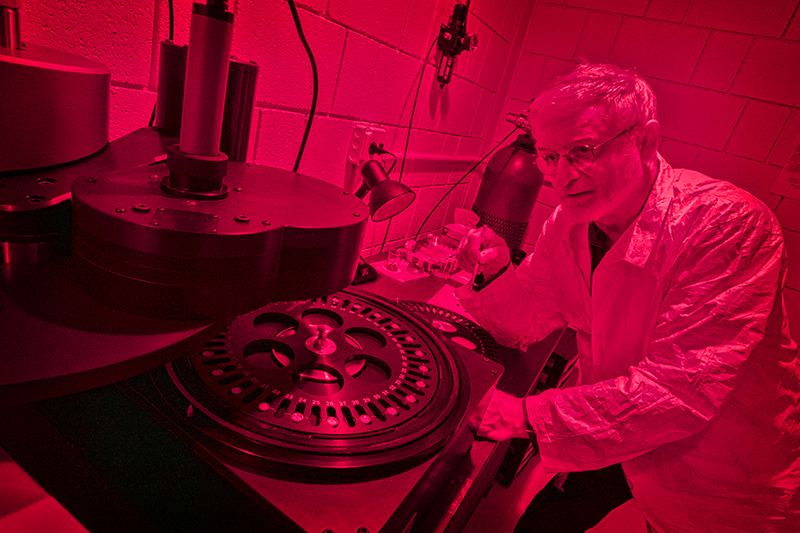 Dan M. Davis, professor and chair of the Department of Geosciences, examines specimens using Optically Stimulated Luminescence in the Laboratory for the Analysis and Dating of Sediment, working in red light to protect the specimens.