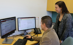 Kristy Bunton  helps faculty member on computer