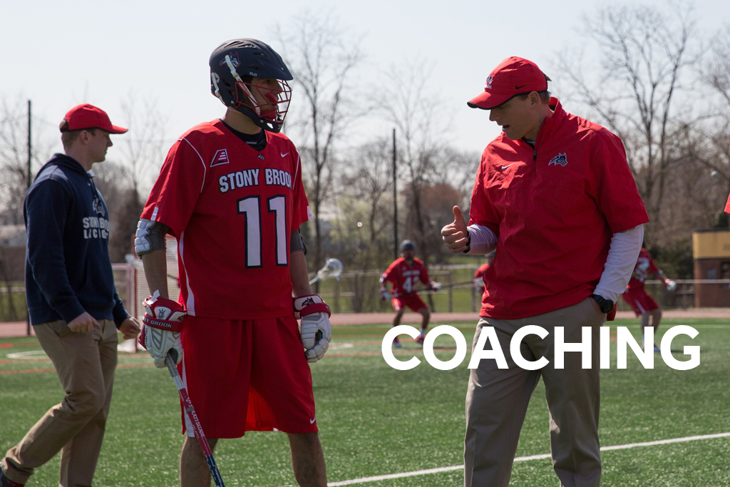 Lacrosse coach speaking with player on the field.