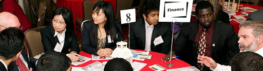 Alumni and students gathered around a table at an event