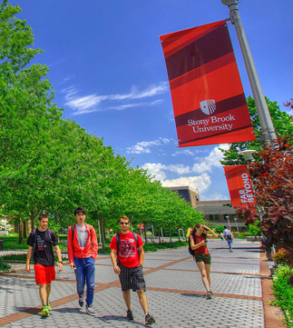 Three students walking through Stony Brook Campus on a beautiful sunny day