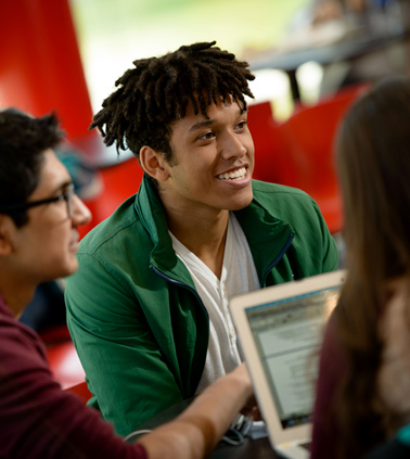 A student smiles as he works with a small group around a round table in the Student Activities Center