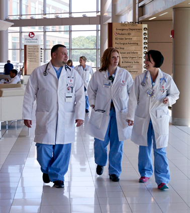 Three Stony Brook Medicine personnel walk through the Hospital as they talk amongst each other