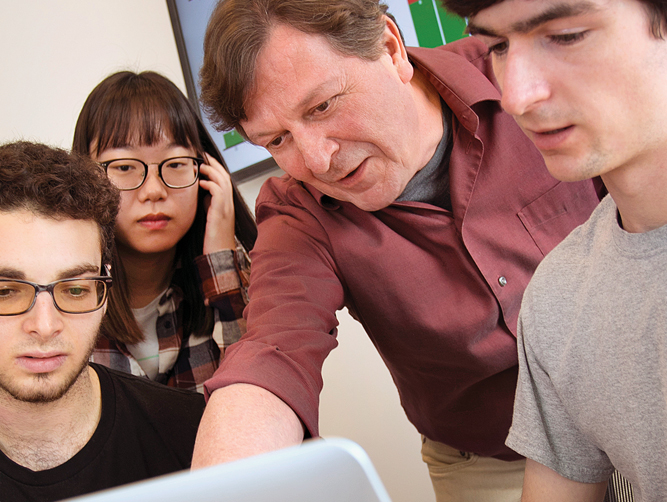 Professor and students looking at computer