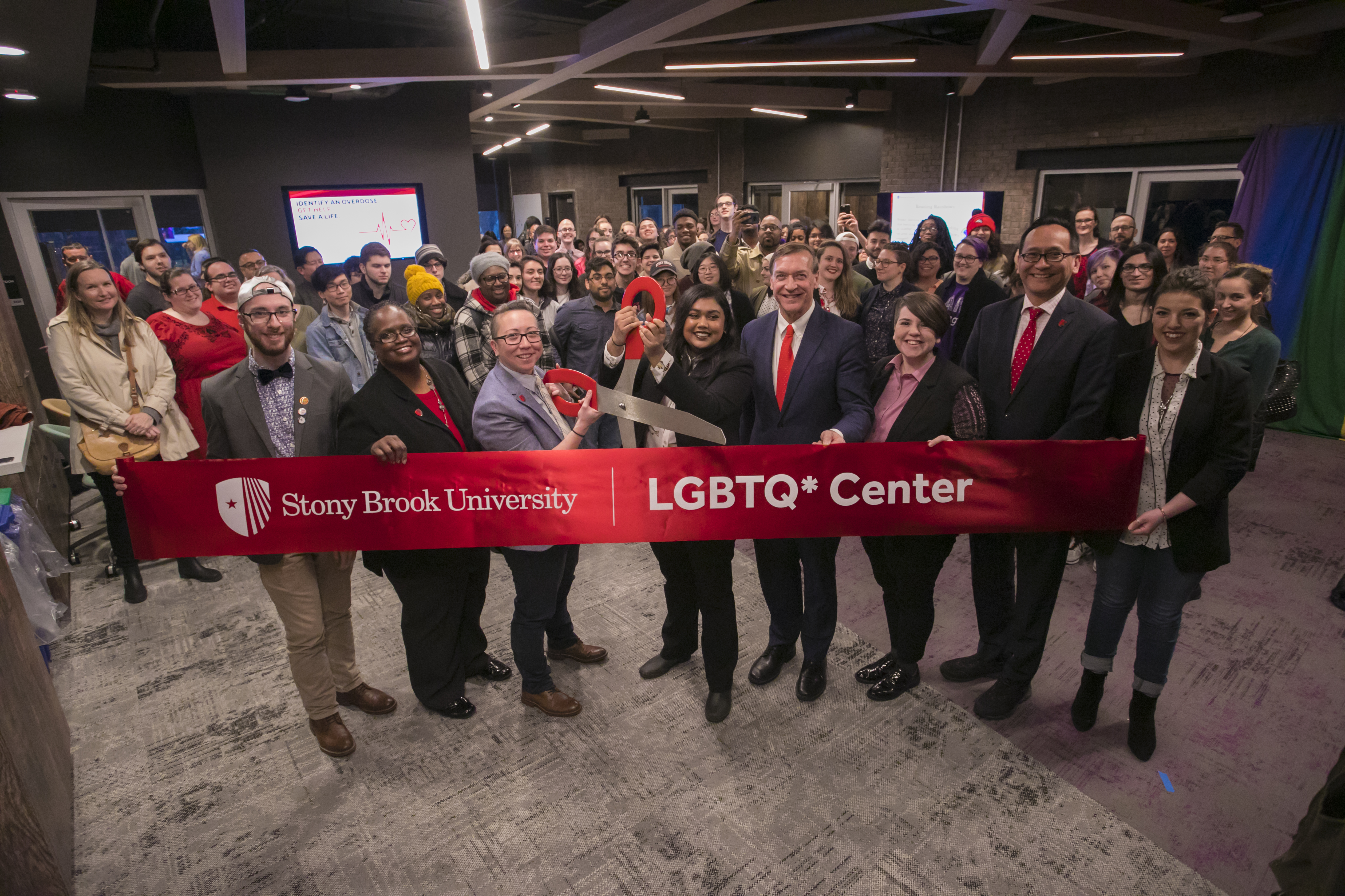 At the LGBTQ* Center grand opening (left to right): Will Argenzio, Cheryl Chambers, Chris Tanaka, Elliot Tanha, President Samuel L. Stanley Jr, El Schneider, Lee Bitsoi and Sydney Gaglio
