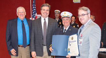 From left: Dr. Reuven Pasternak, CEO, Stony Brook University Hospital; Dr. James A. Vosswinkel, Chief, Division of Trauma, Emergency Surgery and Surgical Critical Care; Firefighter Kevin Peterson; and Dr. Steven Sandoval, Medical Director, Burn Center, receive a proclamation from Suffolk County Executive Steve Bellone.