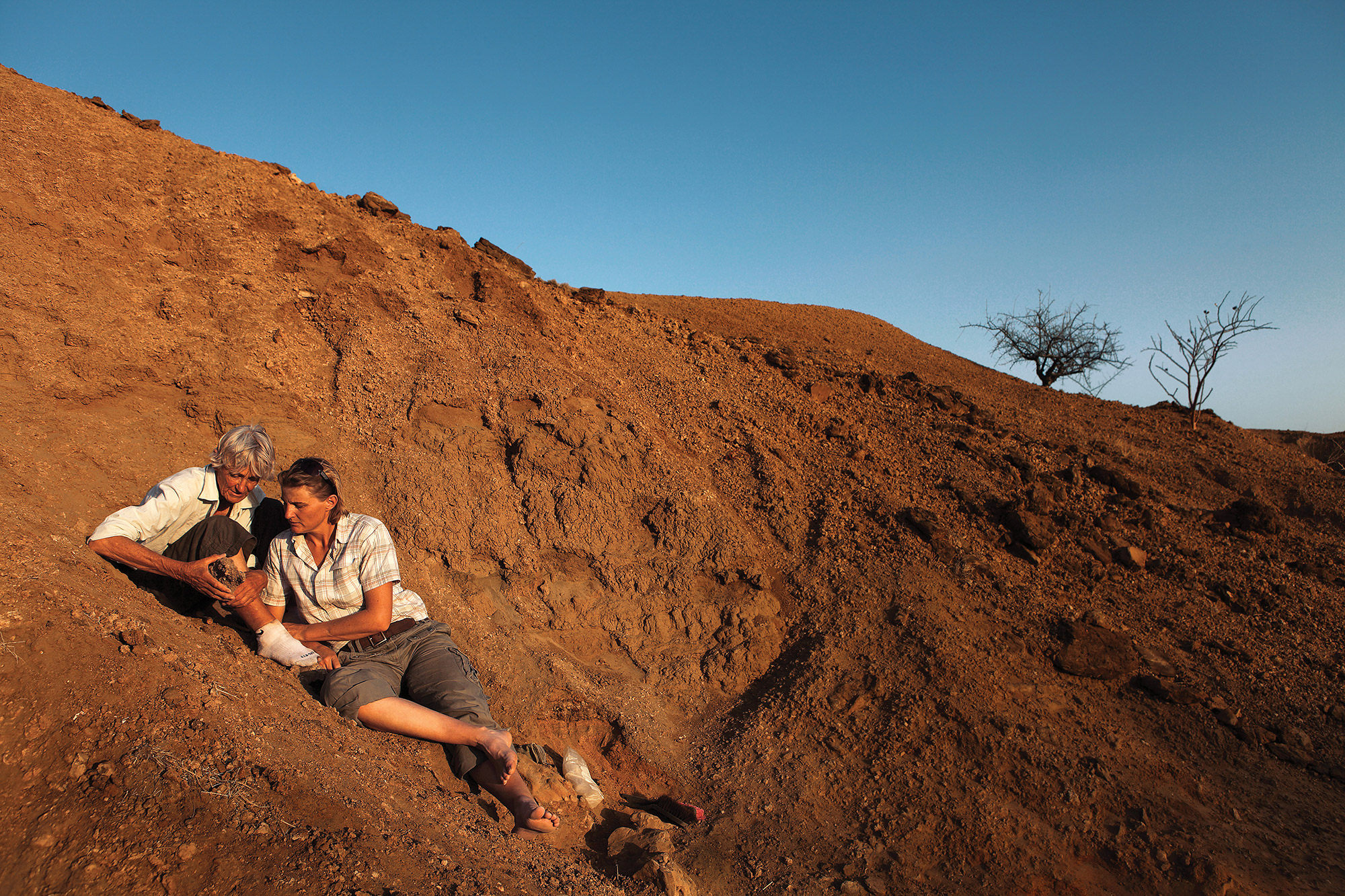 """EXPLORING HUMAN ORIGINS Meave Leakey, left, and daughter Louise Leakey hunt for fossils near the shores of Lake Turkana in Kenya. Stony Brook University's Turkana Basin Institute is the world-renowned base of operations for the Leakeys, who, together with Richard Leakey (not pictured) constitute the """"first family"""" of paleoanthropology. Photo: Mike Hettwer."""