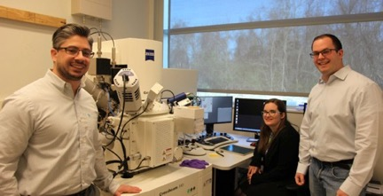 Jason Trelewicz (left) with Olivia Donaldson, who recently graduated with her PhD from Trelewicz's group, and Jonathan Gentile, a current doctoral student, in front of the scanning electron microscope/focused-ion beam at Stony Brook University's Advanced Energy Center.