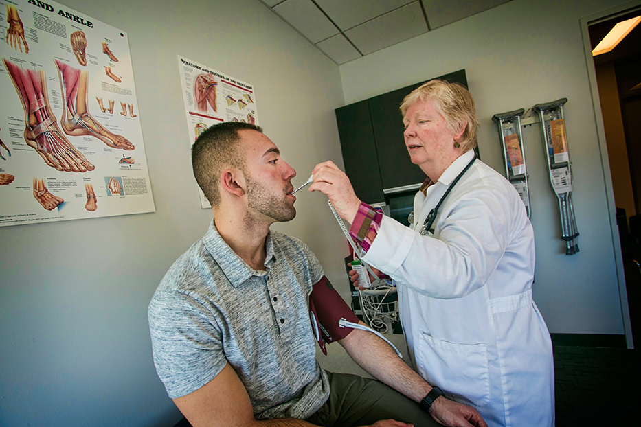 Nurse Practitioner Linda Hamilton examines student Anthony Calzetta-Raymond in the Student Health Walk-In Clinic in the Campus Recreational Center.