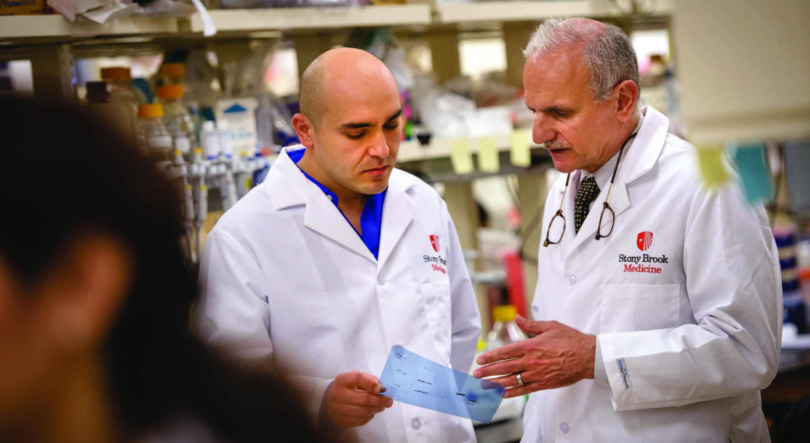 Cancer Center Director Yusuf A. Hannun, MD (right) discusses a result with Research Assistant Professor Can Senkal.