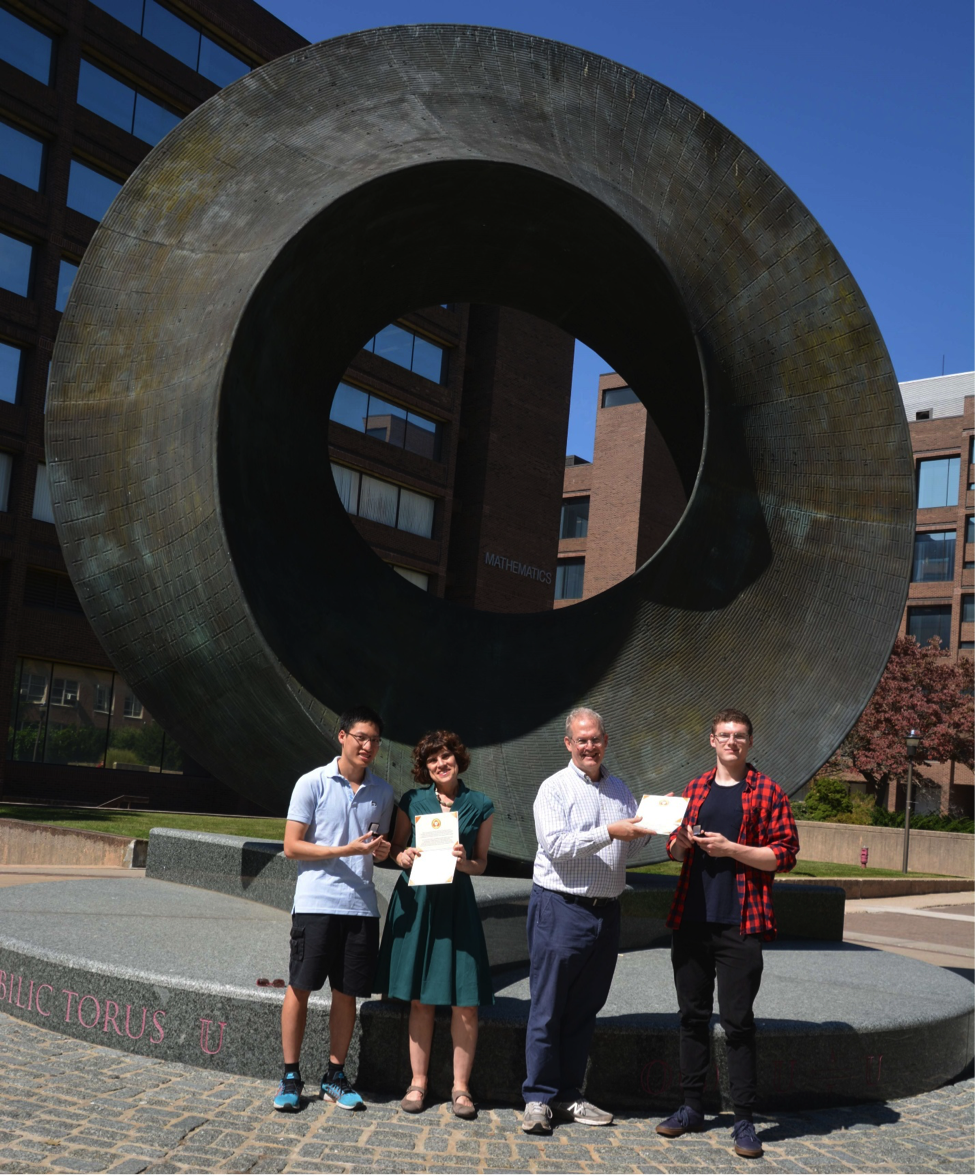 Summer Math Scholarship inaugural recipient Minh Nguyen, Stony Brook University Mathematics Department Professor Moira Chas, Stony Brook University Mathematics Department Chair Robert Lazarsfeld and second recipient Hubert Puszklewicz holding their certificates from The Summer Math Foundation.