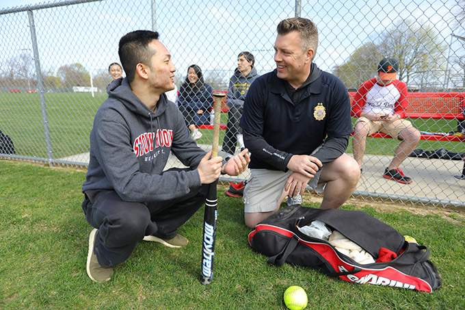 Assistant Chief of Police Eric Olsen and USG President Cole Lee '17 talk softball at Field Day with UPD. (Photo by John Griffin)